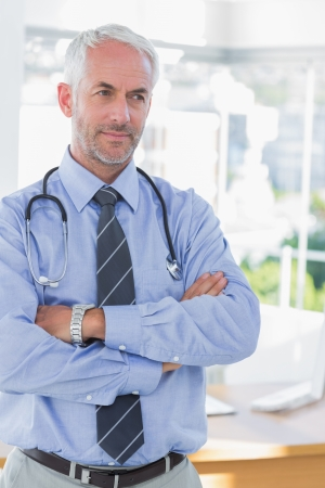 Doctor with arms folded looking away photo