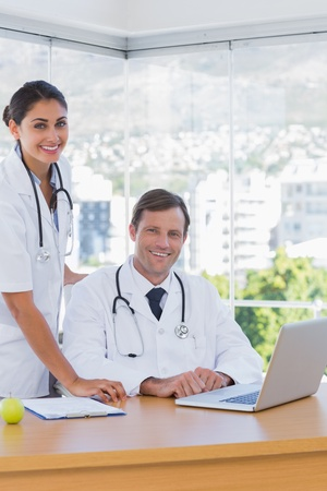 Cheerful doctors posing together in their office with a laptop on the desk photo