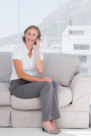 Smiling businesswoman phoning and sitting on sofa photo