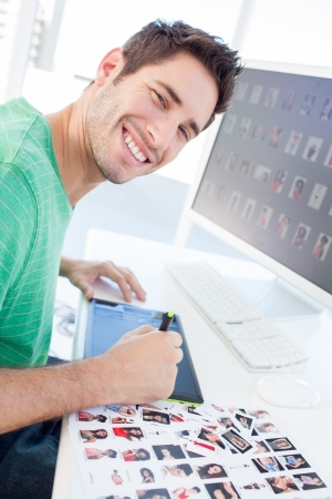 Photo editor working with a graphics tablet in a modern office photo