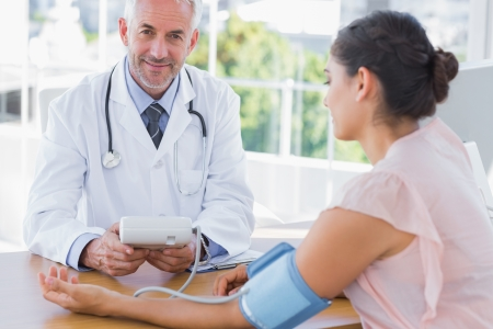 Smiling doctor taking the heartbeat of a patient in the office photo