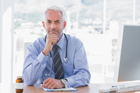 Cheerful doctor sitting behind his desk at the office photo
