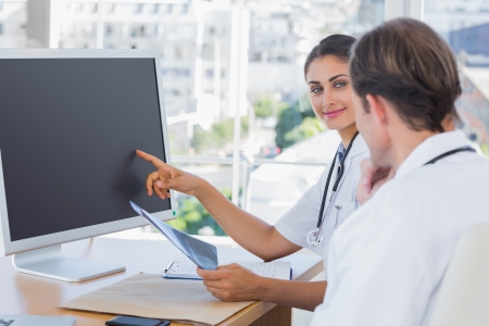 Doctor showing the screen of a computer to a colleague while they are working together photo