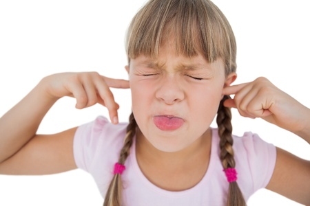 Little girl clogging her ears on white background