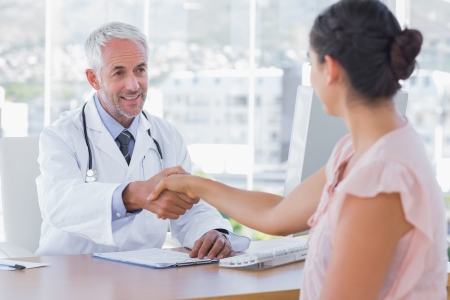 Doctor shaking hands to patient in the office at desk photo