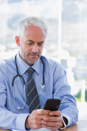 Attractive doctor typing a text message on his smartphone photo