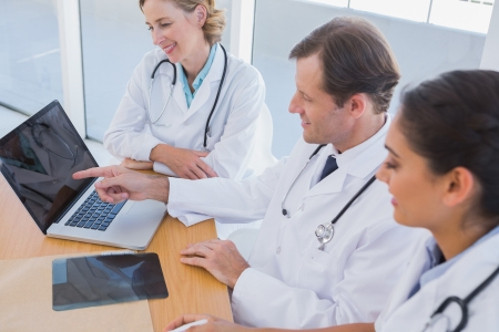 Smiling doctor showing laptop screen to colleagues while they are working together photo