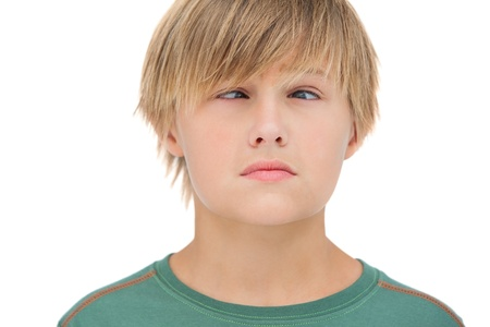 wincing: Little boy wincing on white background  Stock Photo