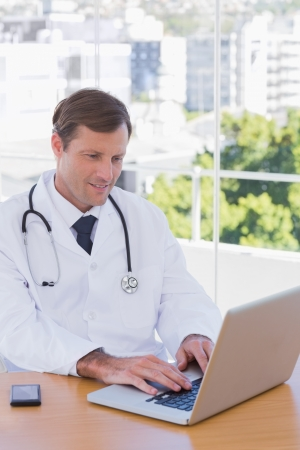 Cheerful doctor working on a laptop in his office photo