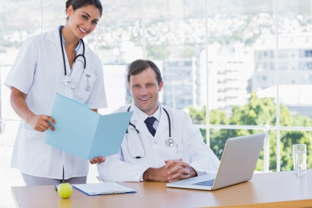 Pretty doctor showing a folder to a colleague sat at his desk photo