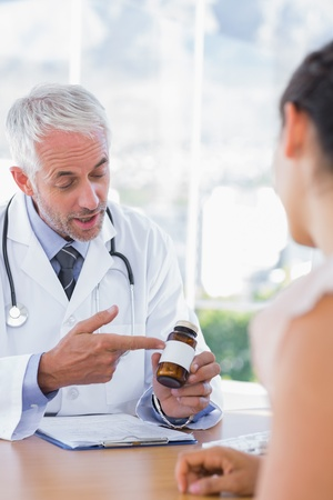 Doctor showing bottle of pills to patient in the office at desk photo