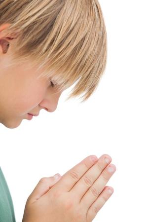 Little boy praying with eyes closed on white background  photo