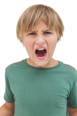 Furious little boy shouting on white background  photo