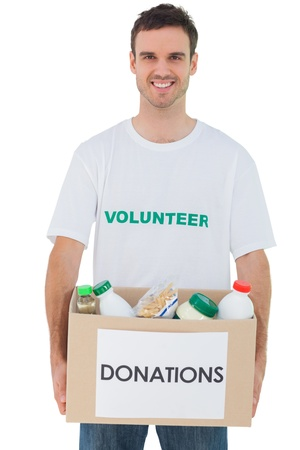 Handsome man carrying donation box with food on white background photo