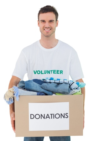 Attractive man holding donation box with clothes on white background photo