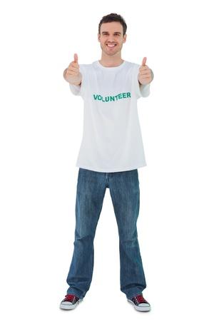 altruism: Atractivo hombre llevaba camiseta voluntario dando pulgar hacia arriba sobre fondo blanco Foto de archivo