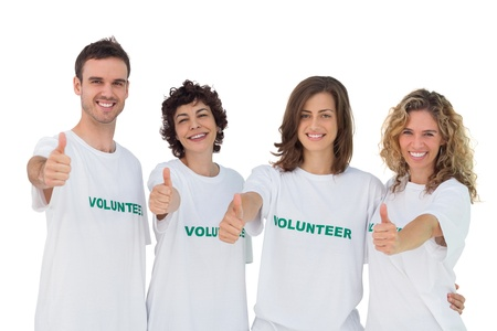 volunteerism: Cheerful group of volunteers giving thums up on white background Stock Photo