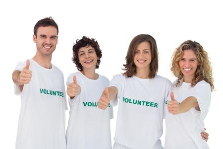 altruismo: Grupo alegre de los voluntarios dando thums en el fondo blanco