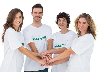 altruismo: Sonriendo grupo de voluntarios acumulando sus manos en el fondo blanco