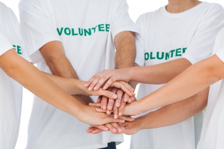 volunteerism: Group of volunteers putting hands together on white background