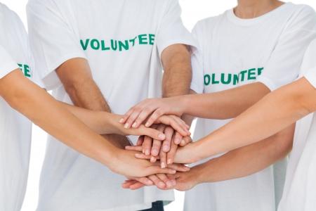mani unite: Gruppo di volontari di mettere le mani insieme su sfondo bianco