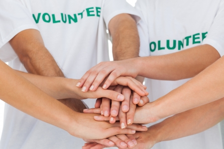 piling: Group of volunteers piling up their hands together