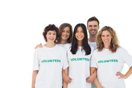 altruism: Grupo sonriente de voluntarios de pie en el fondo blanco