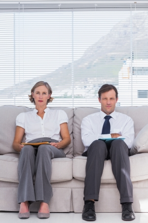 Stern business people sitting on couch in office photo