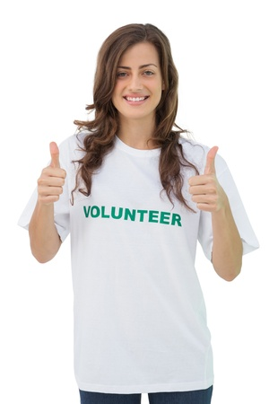 Happy volunteer giving thumbs up on white background photo