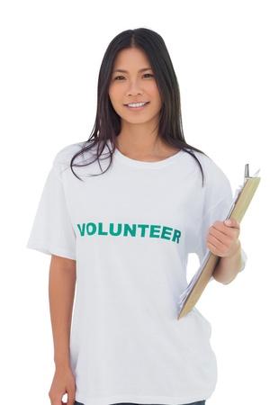 altruismo: La mujer llevaba voluntario camiseta celebraci�n portapapeles en el fondo blanco Foto de archivo