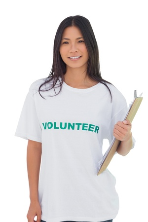 altruism: Woman wearing volunteer tshirt holding clipboard on white background