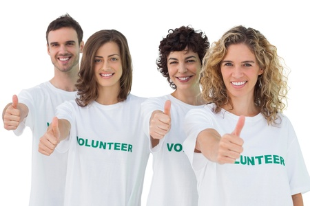 volunteerism: Group of volunteers giving thumbs up on white background Stock Photo