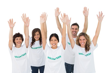 volunteerism: Group of volunteers raising arms on white background Stock Photo