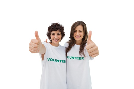 Two happy volunteers giving thumbs up on white background photo