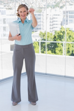 dangling: Happy estate agent showing house keys standing in office Stock Photo