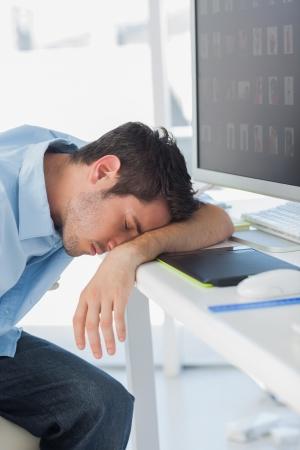 Graphic designer dorme sulla sua tastiera nel suo ufficio