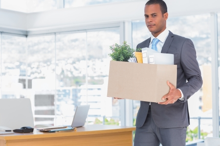 forlorn: Sad businessman leaving his company while he is holding a box Stock Photo