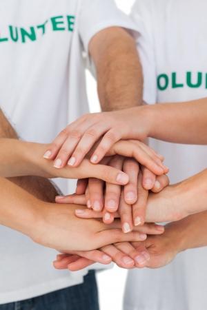 ensemble mains: Les b�n�voles mettent les mains sur fond blanc Banque d'images