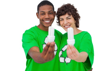 Two environmental activists holding energy saving light bulbs on white background photo