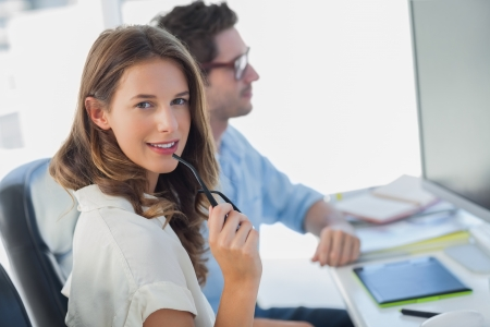 Attractive photo editor biting her reading glasses next to a colleague Stock Photo - 20636229