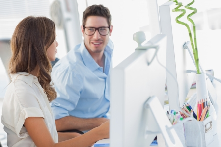 Smiling designers discussing together in their office Stock Photo - 20635700