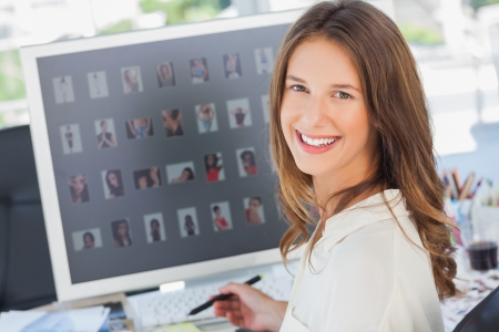 editor: Portrait of a smiling photo editor working at her desk Stock Photo