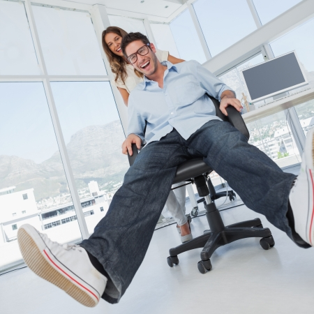 Smiling designers having fun with on a swivel chair in their office photo