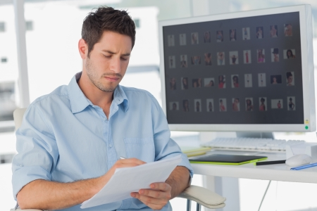 editor: Photo editor writing on documents in his office Stock Photo