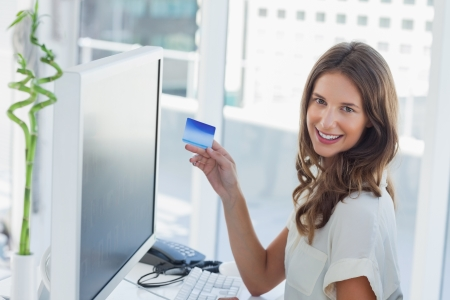 Cheerful brunette designer purchasing online with her credit card photo
