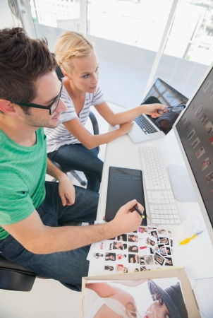 Cheerful photo editors working together on graphics tablet in their office Stock Photo - 20637755