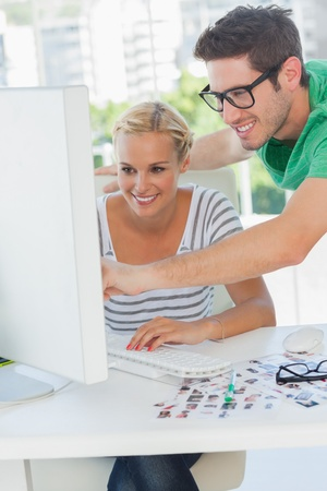 editor: Cheerful photo editor pointing at a computer with a colleague Stock Photo