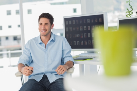 editor: Cheerful photo editor in his swivel chair in his office