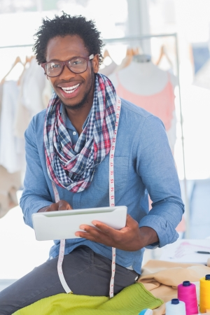 fashion industry: Handsome fashion designer using digital tablet and looking at camera Stock Photo