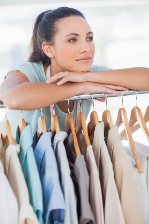 clothes rail: Fashion designer leaning on clothes rail in a studio